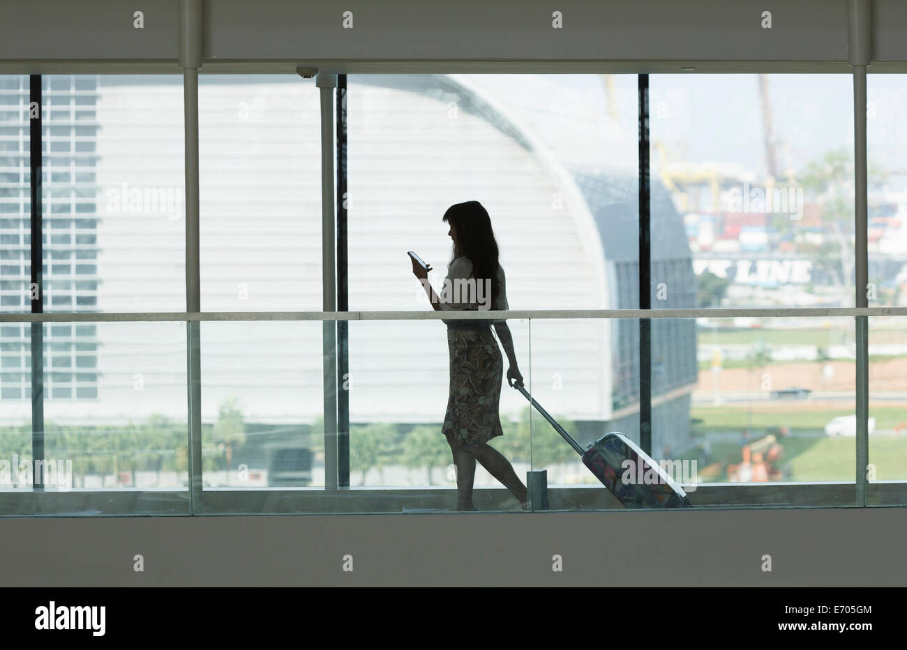 Young woman using smartphone and pulling suitcase in airport - Stock Image