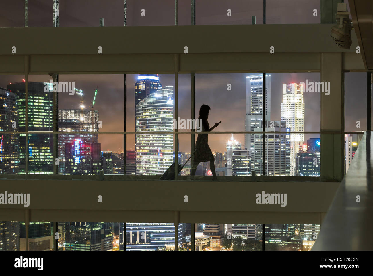 Young woman using smartphone and pulling suitcase, city skyline in view - Stock Image
