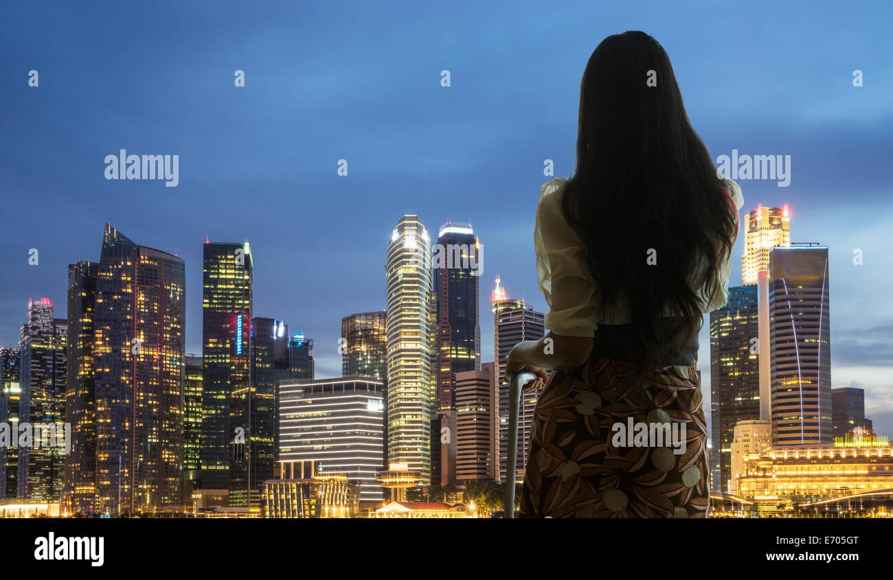 Young woman with suitcase looking at city skyline - Stock Image