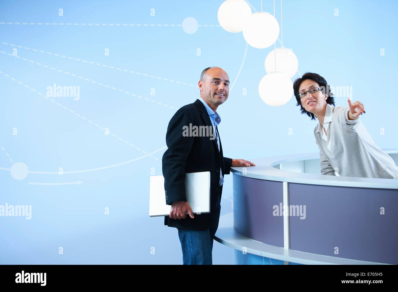 Mature adult man asking receptionist for directions - Stock Image