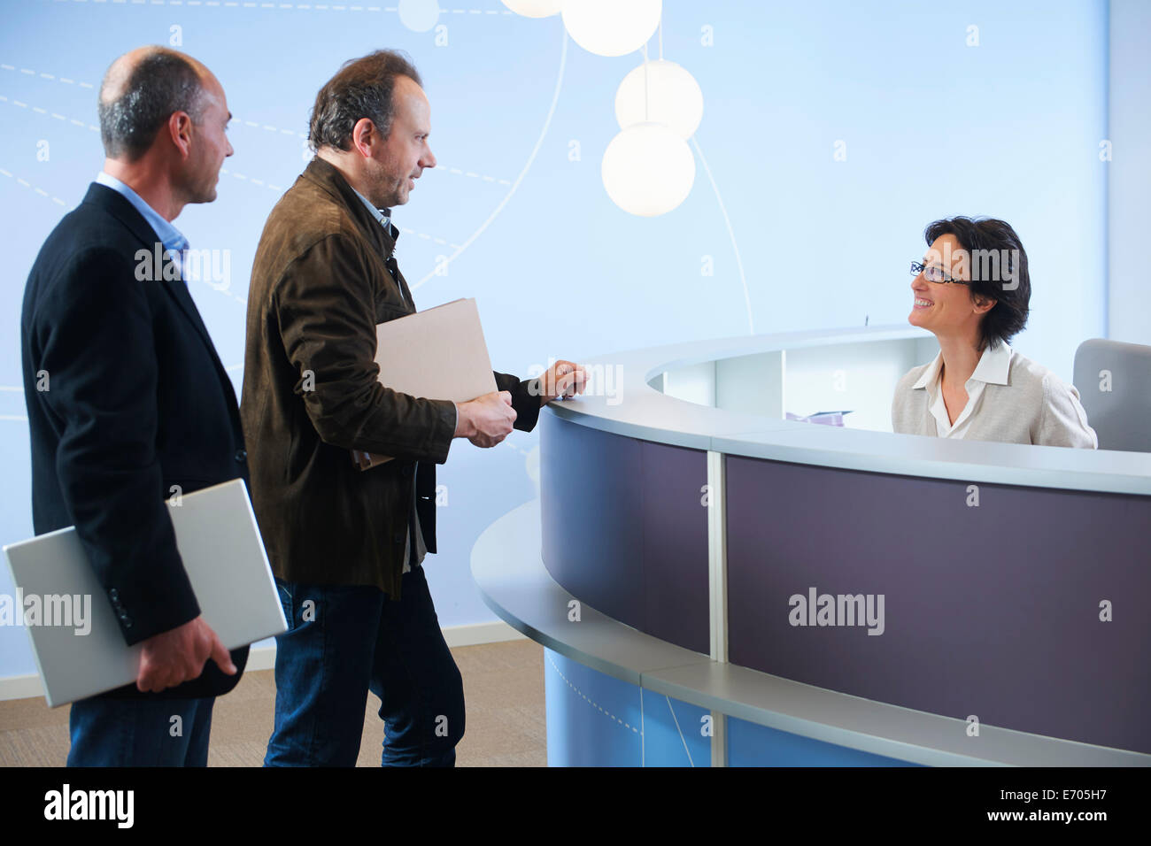 Two mature adult men speaking to receptionist - Stock Image