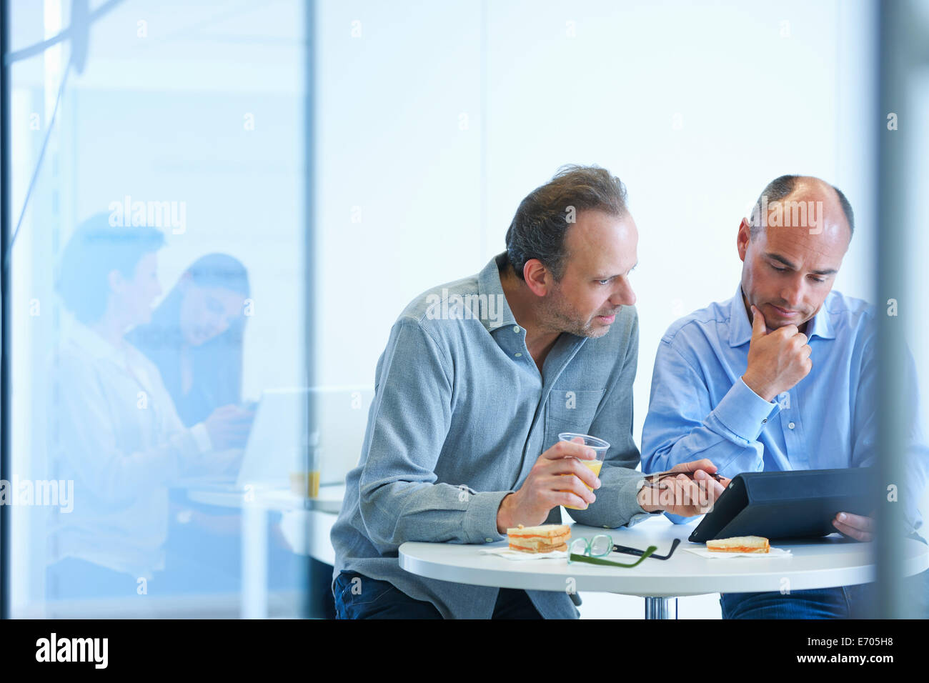 Business people having discussion over lunch - Stock Image
