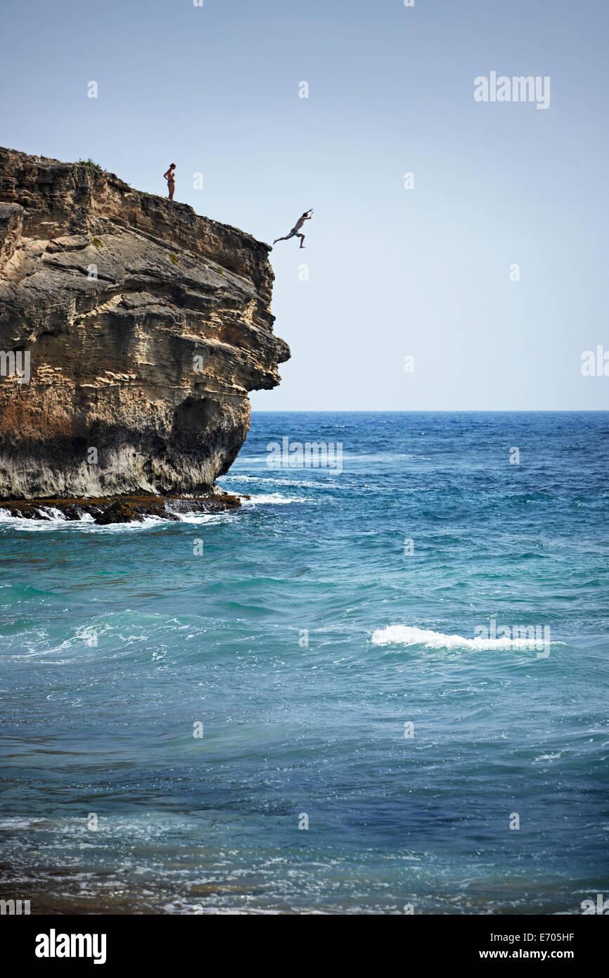 Man jumping into sea from cliff, Poipu, Kaua'i, Hawaii, USA - Stock Image