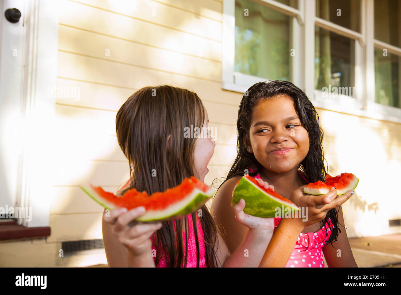 Two smiling girls sitting on house porch with slices of watermelon - Stock Image