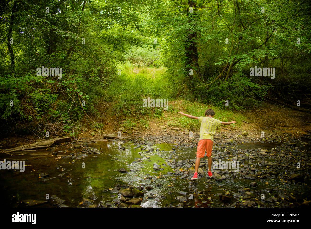 Boy at edge of stream - Stock Image