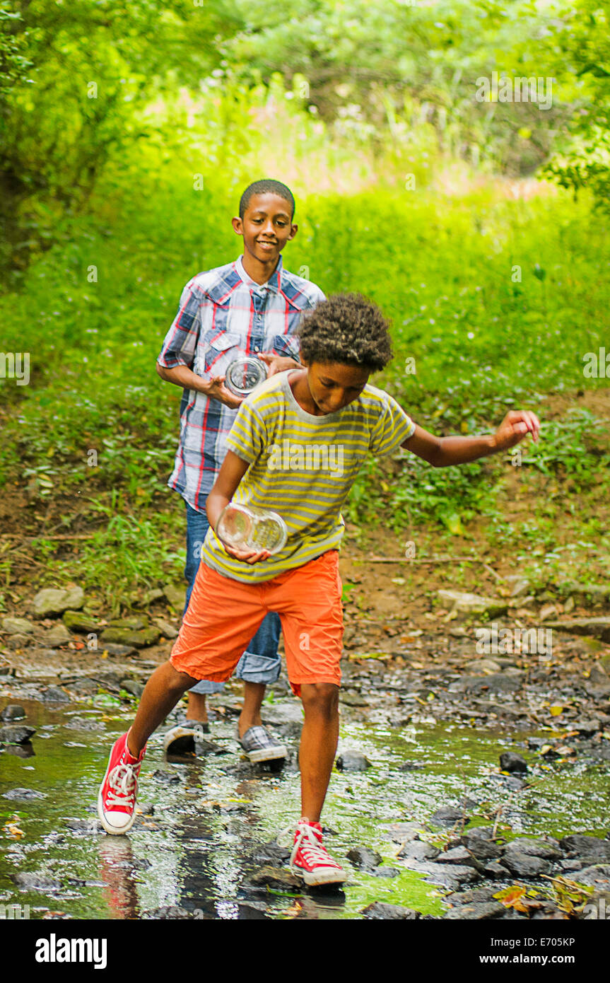Two boys at edge of stream - Stock Image