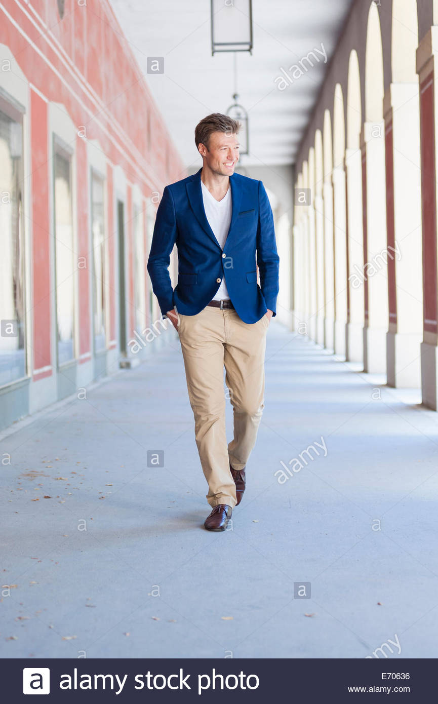 Mid adult male strolling in city shopping mall Stock Photo