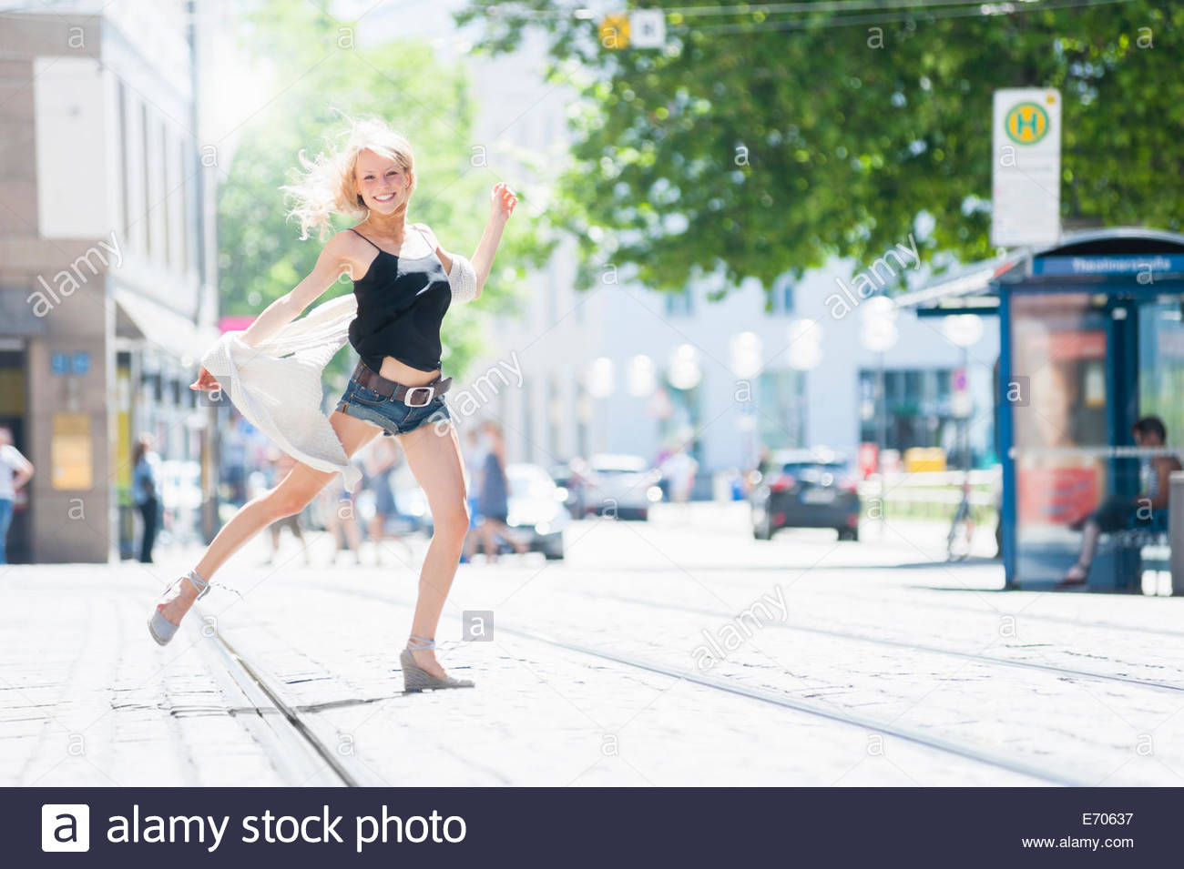 Confident young woman dancing on city street - Stock Image