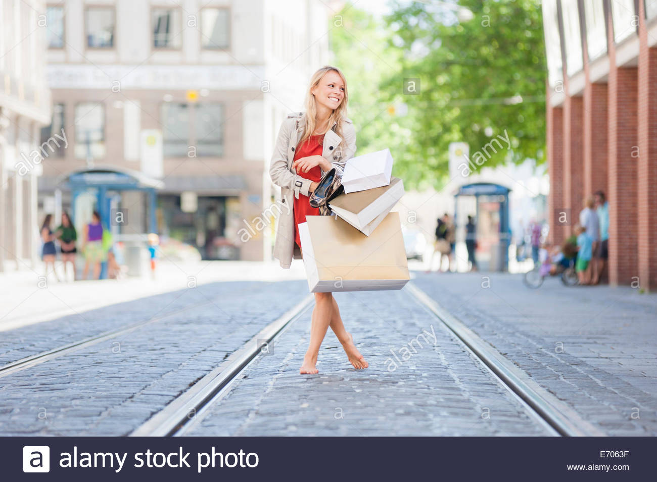 Young woman carrying shopping bags on city street - Stock Image