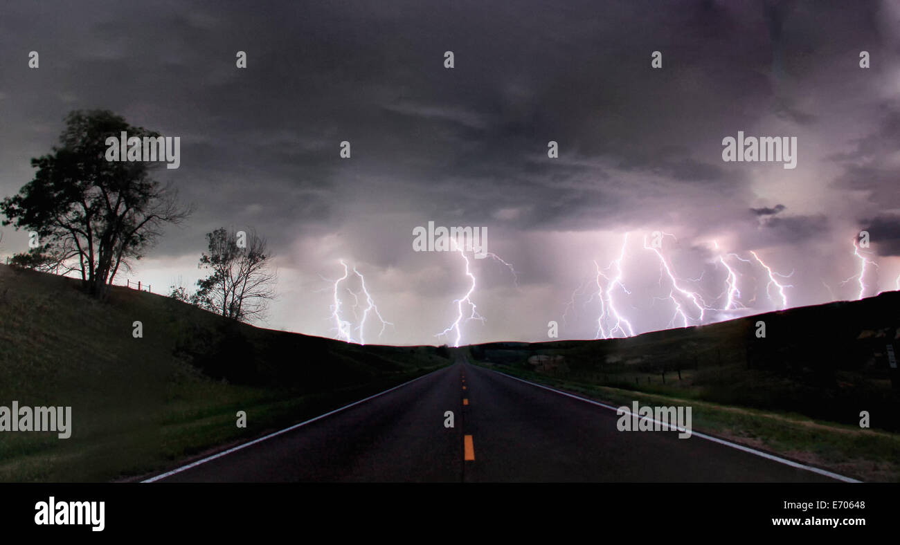A composite image from 5 images of cloud-to-ground lightening bolts at the end of a rural road, Lexington, Nebraska, - Stock Image