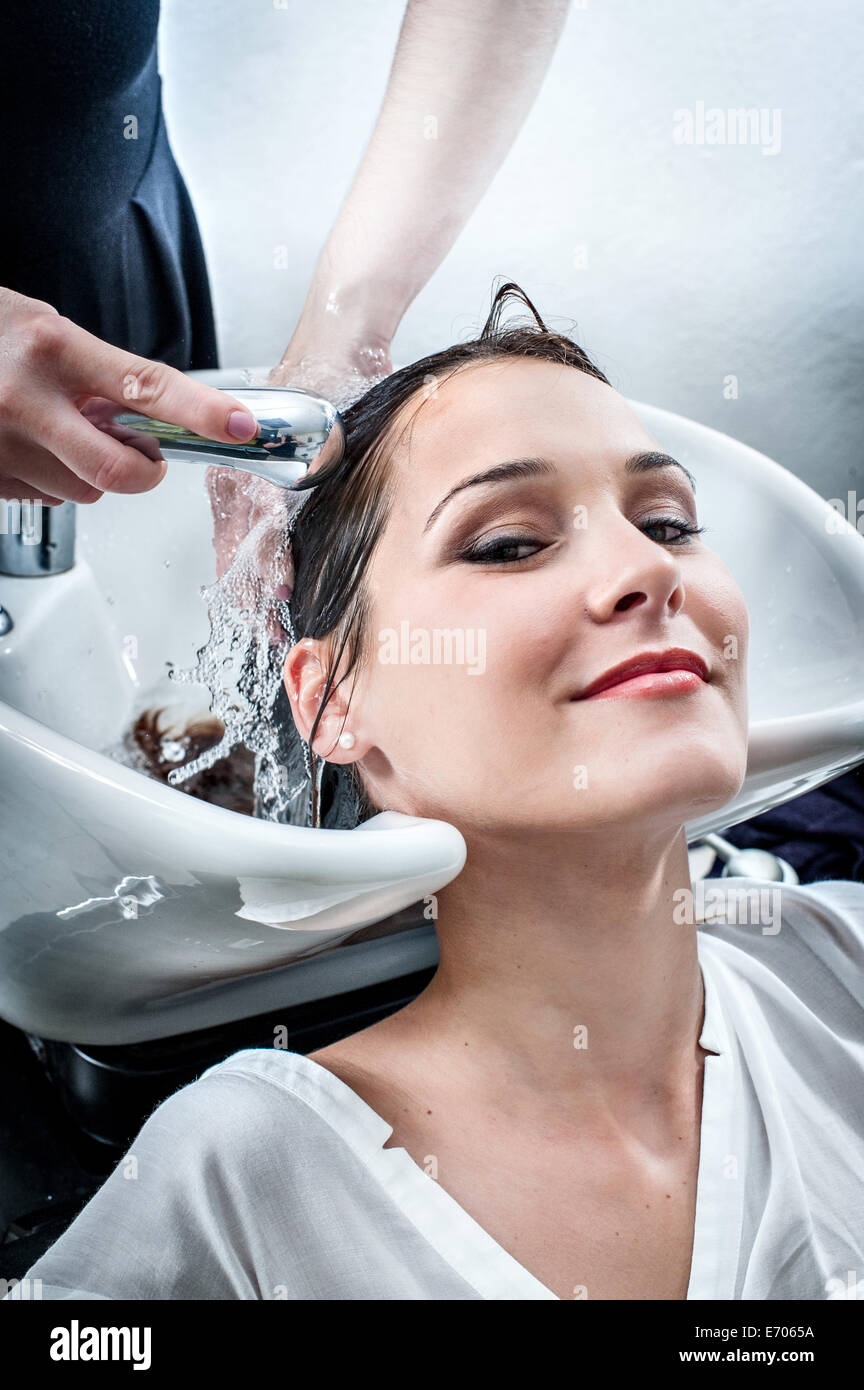 Female hairdresser washing young woman's hair in hair salon - Stock Image