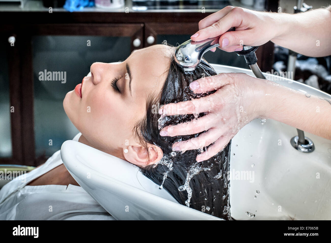 Female hairdresser rinsing young woman's hair in hair salon - Stock Image
