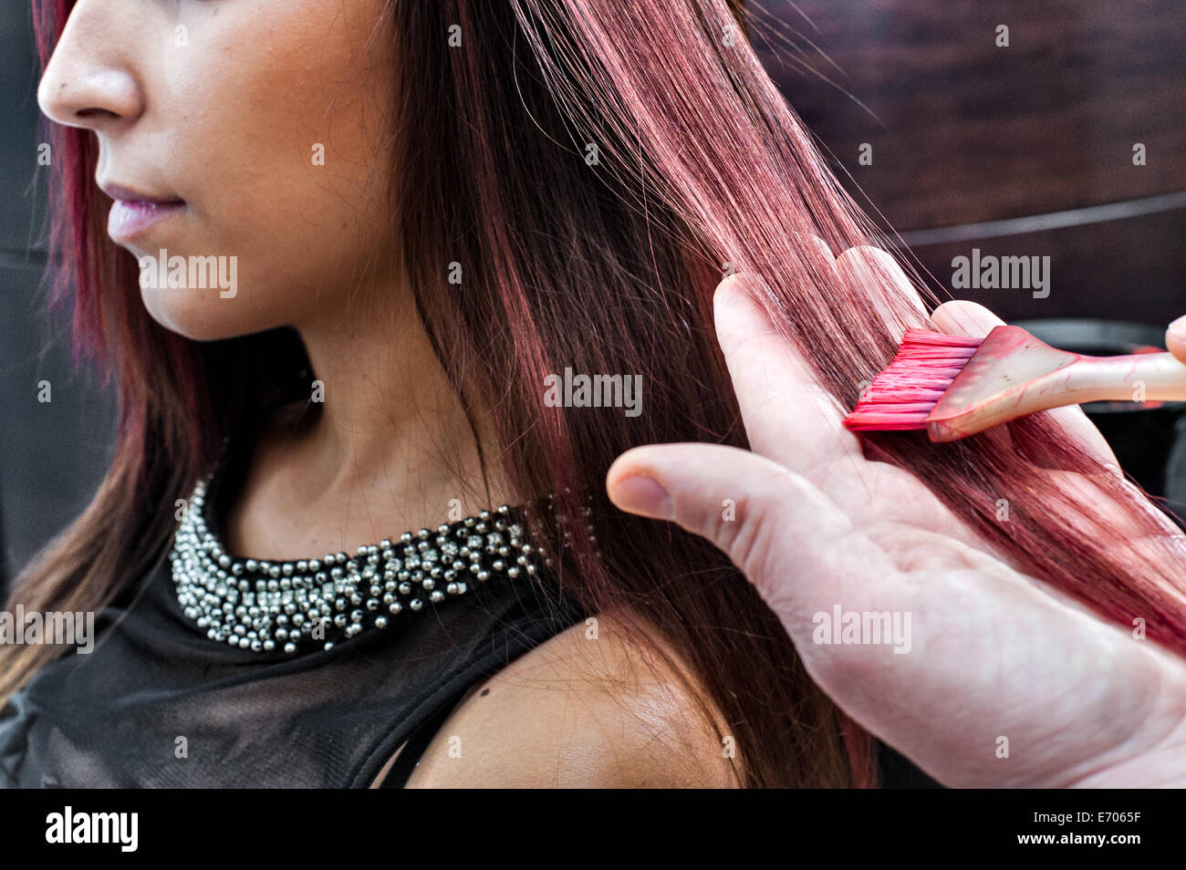 Male hairdresser dyeing young woman's hair pink color in hair salon - Stock Image