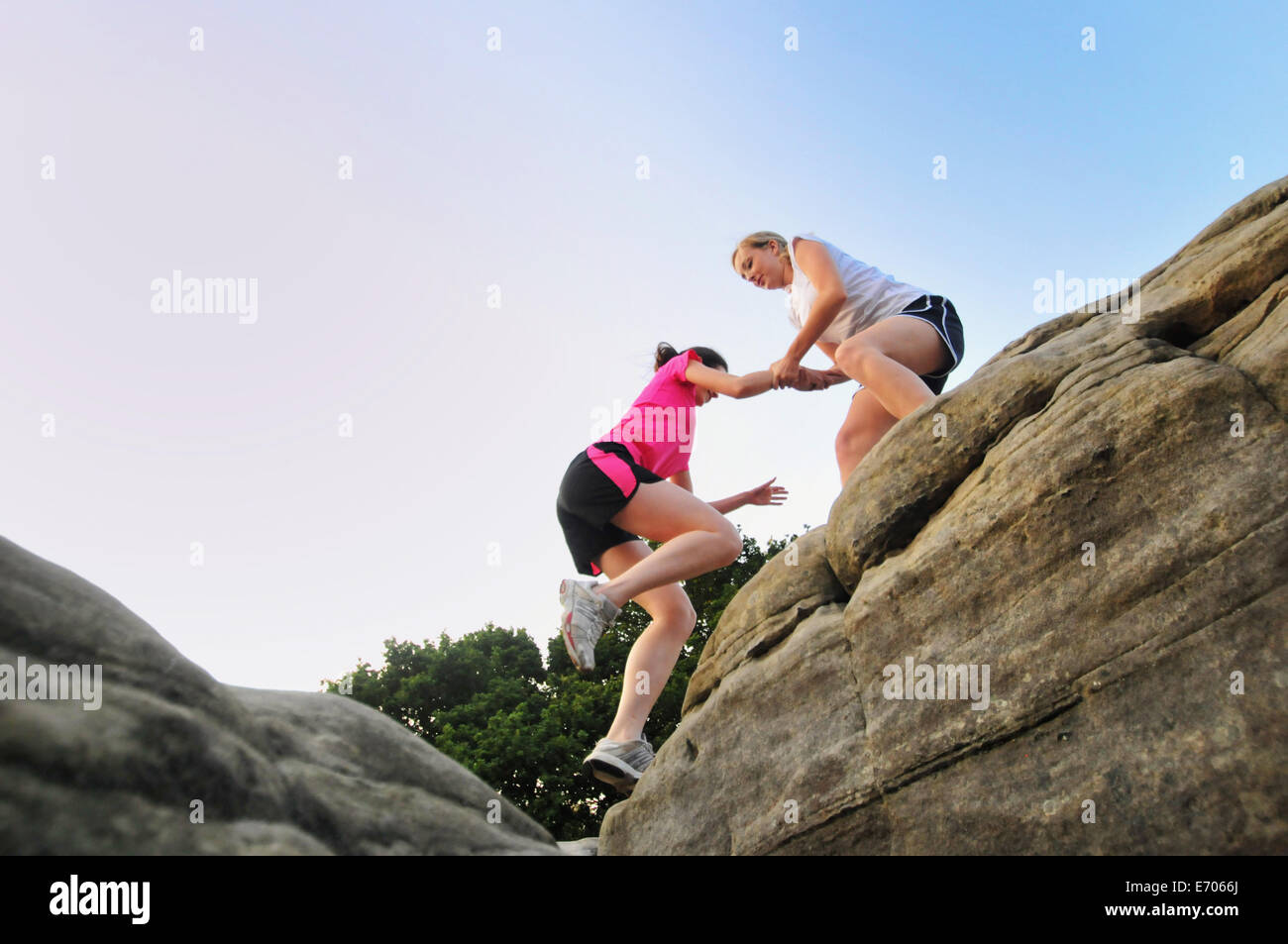 Two young women runners helping each other on top of rock formation - Stock Image