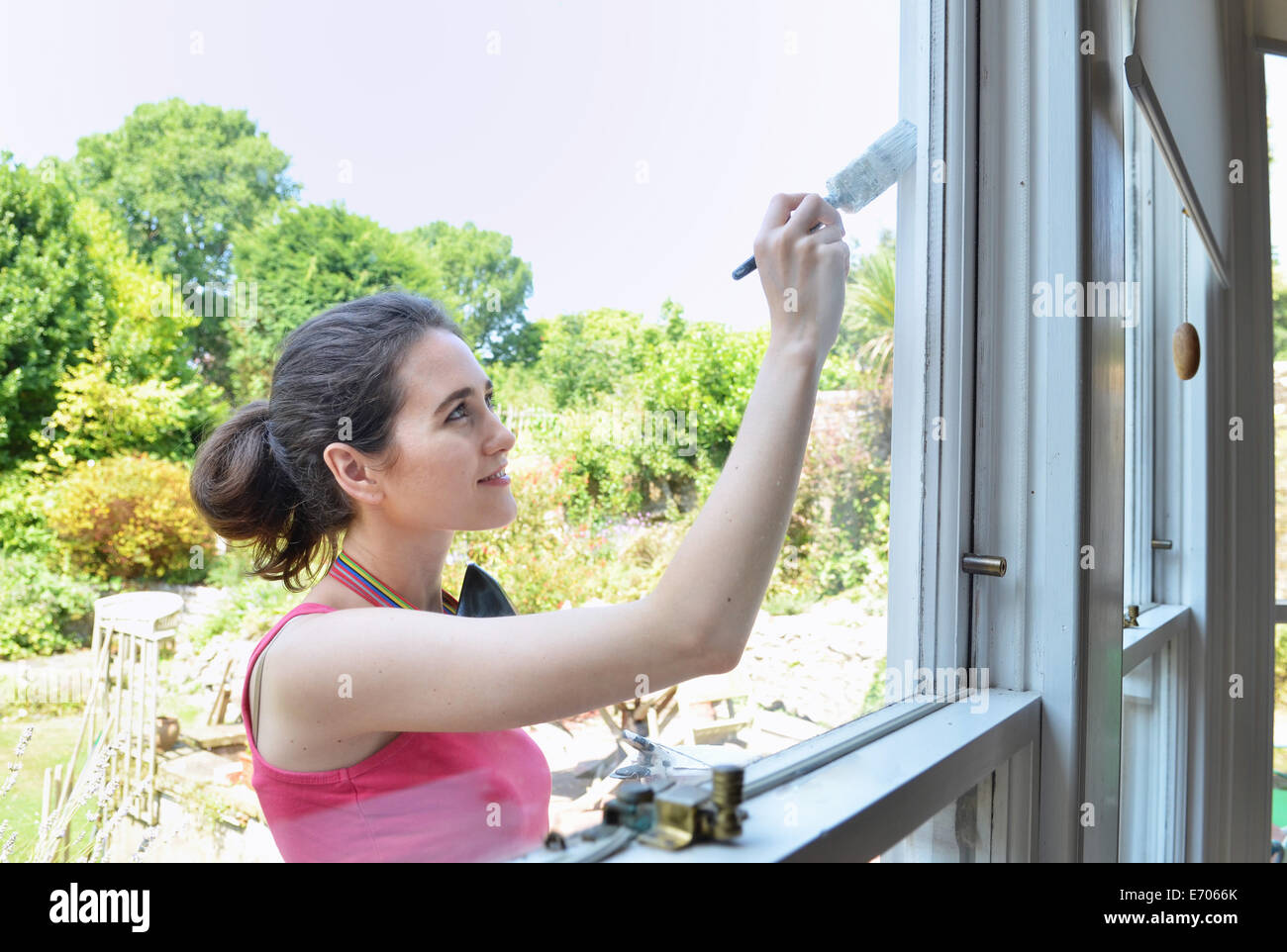 Young woman painting house window - Stock Image