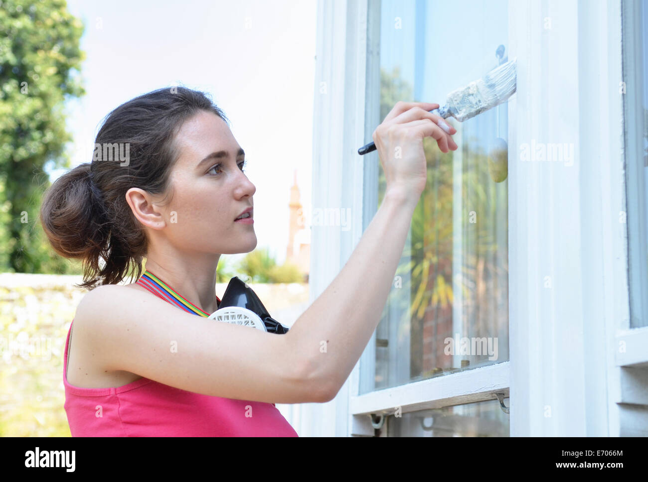 Young woman painting window of house - Stock Image