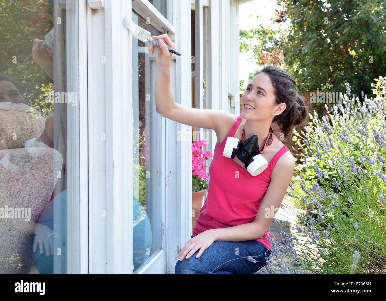 Young woman sitting painting house window - Stock Image