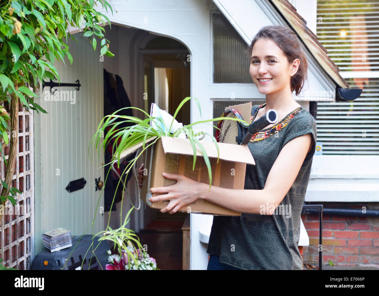Young woman outside new house carrying cardboard box - Stock Image