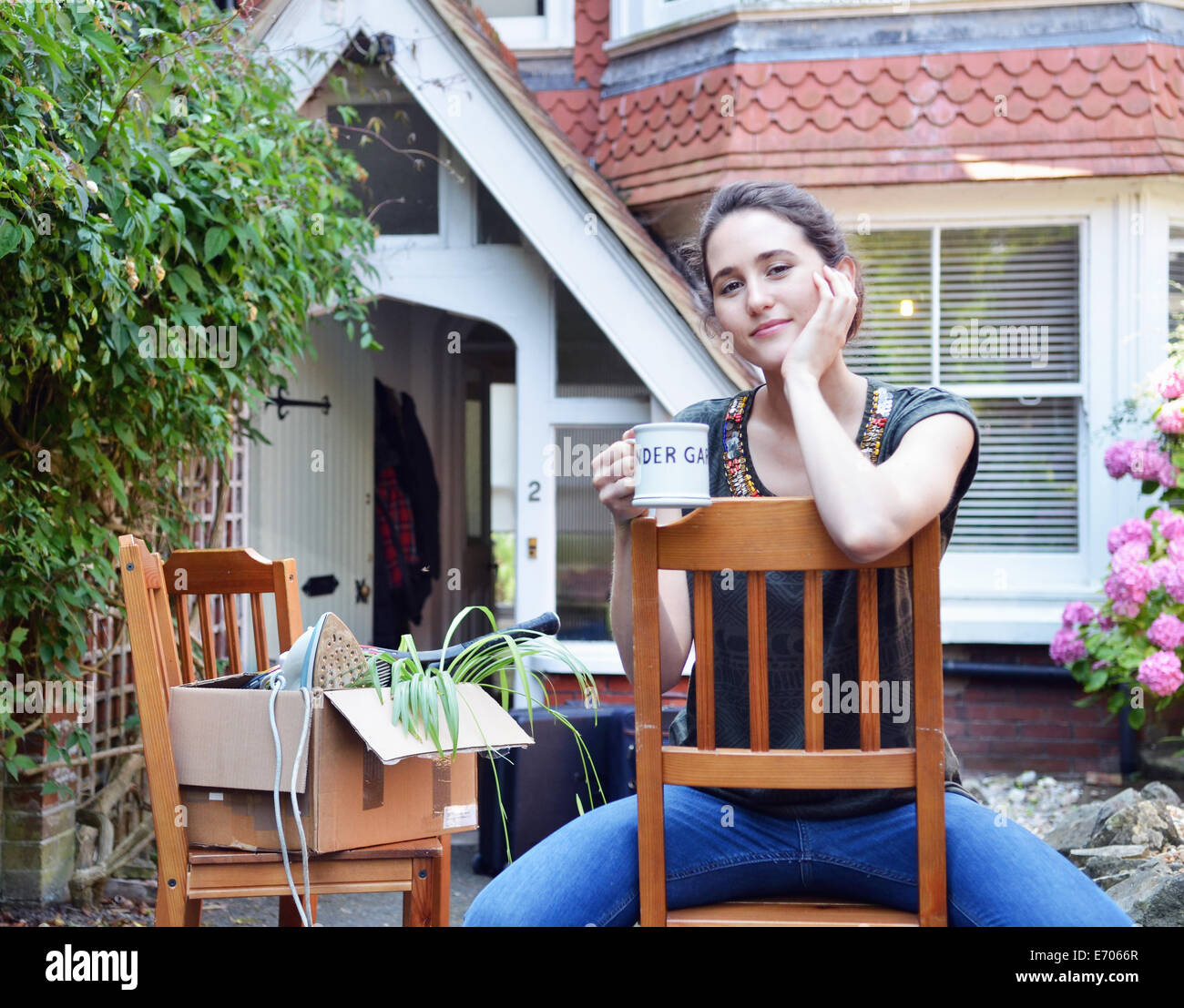 Portrait of young woman taking a coffee break outside new house - Stock Image