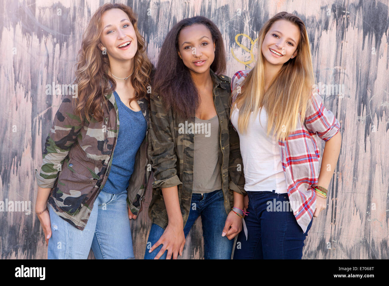 Teenage girls by wall with drip mark pattern - Stock Image