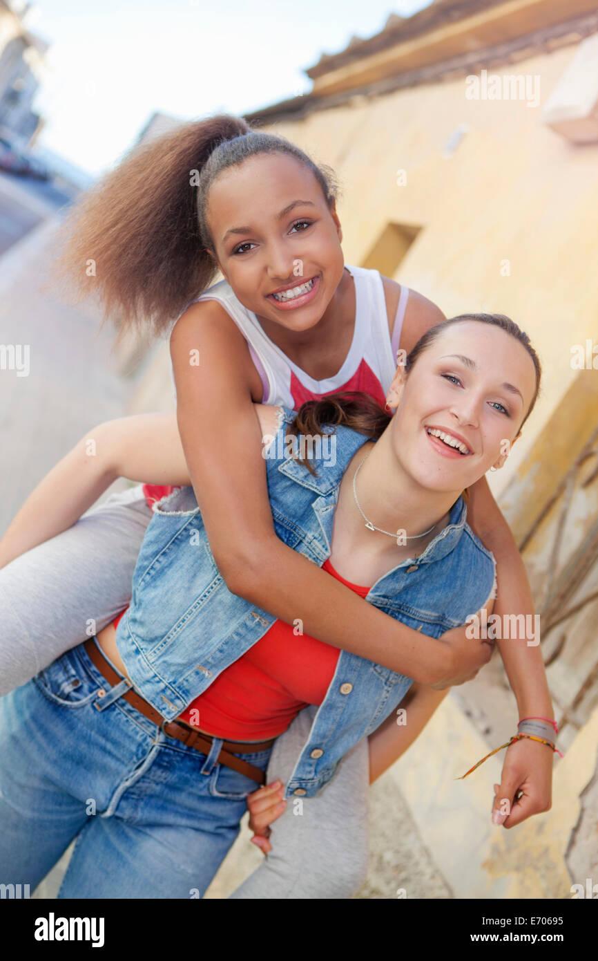 Teenage girl giving friend piggyback ride - Stock Image