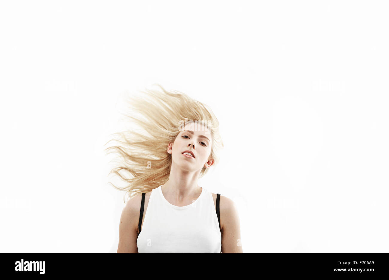 Studio portrait of young woman shaking long blond hair - Stock Image