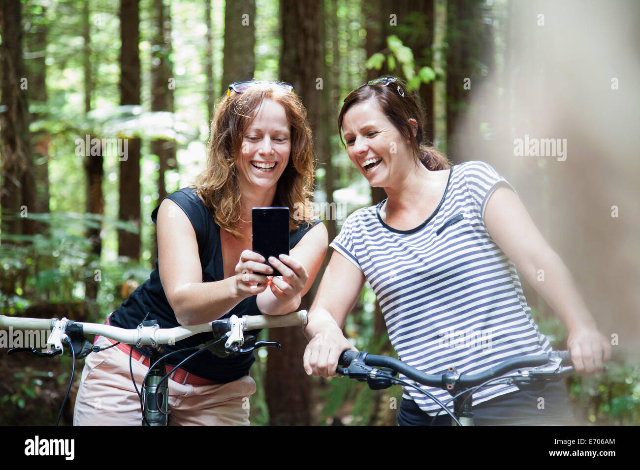 Two women mountain bikers looking at smartphone in forest - Stock Image
