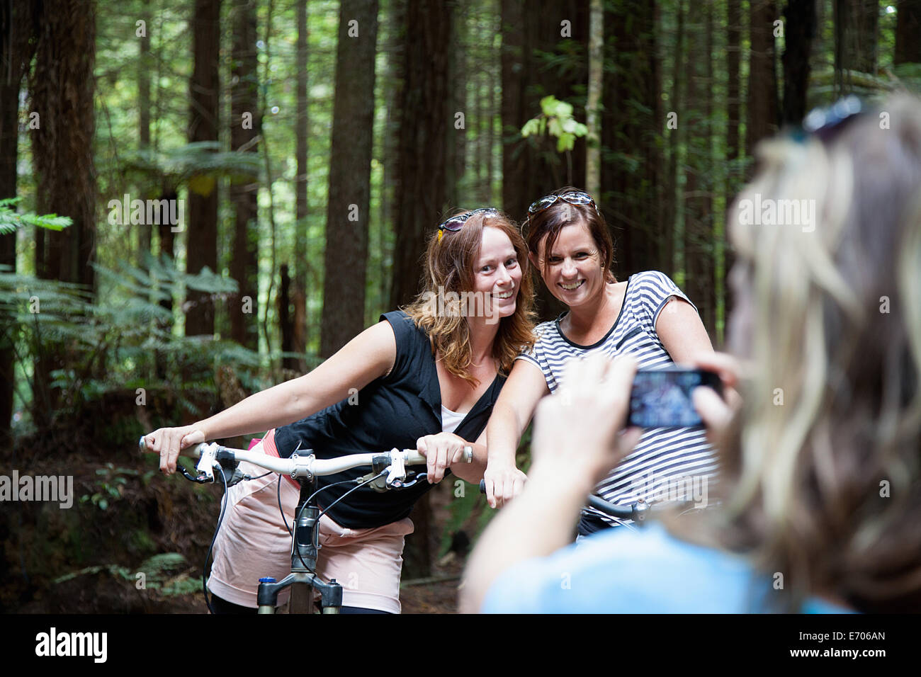 Over shoulder view of women mountain bikers posing for photograph on smartphone in forest - Stock Image