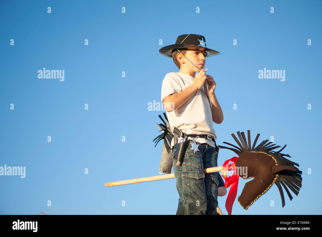 Boy dressed as cowboy fastening hat - Stock Image