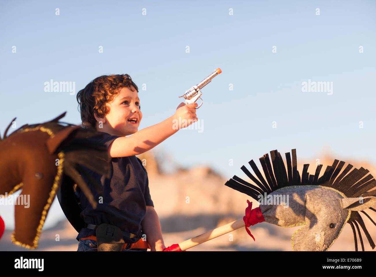 Boy dressed as cowboy with hobby horse and toy gun in sand dunes - Stock Image