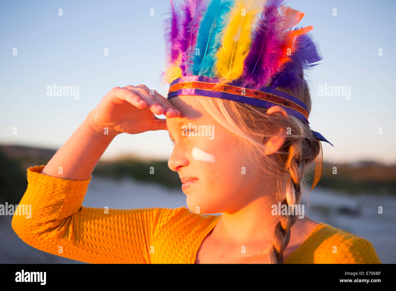 Close up of girl dressed as native american in feather headdress with hand shading eyes - Stock Image