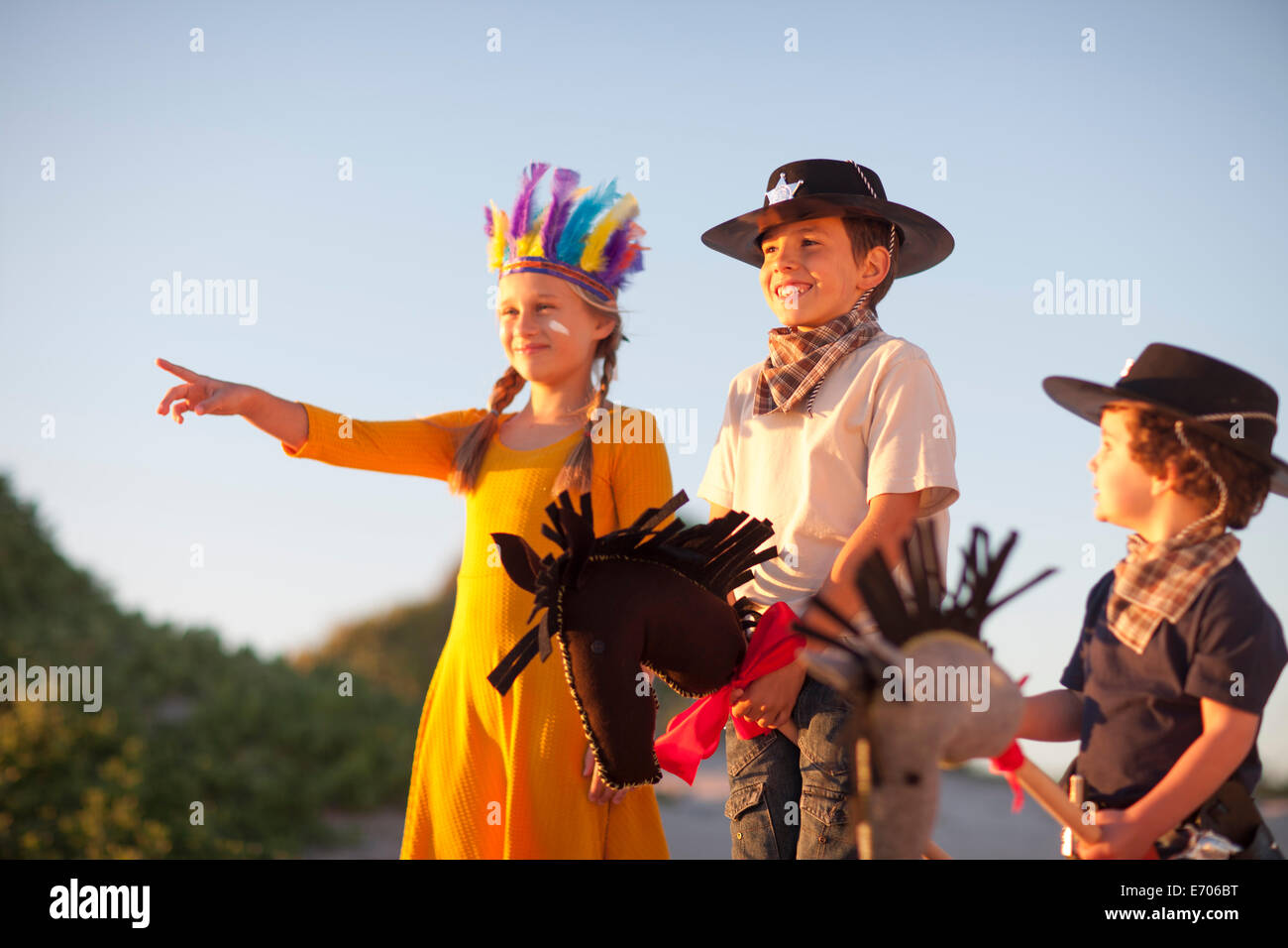 Three children dressed as native american and cowboys pointing from sand dunes - Stock Image