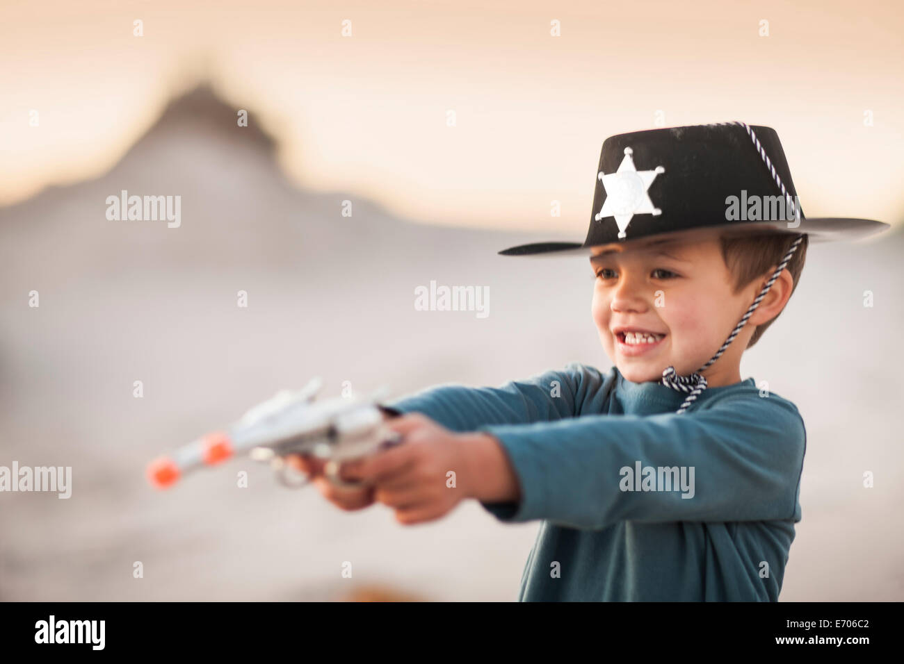 Boy dressed as cowboy sheriff holding pointing toy guns in sand dunes - Stock Image
