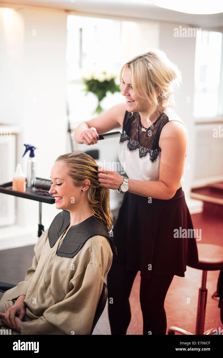 Hairdresser combing customer's hair - Stock Image