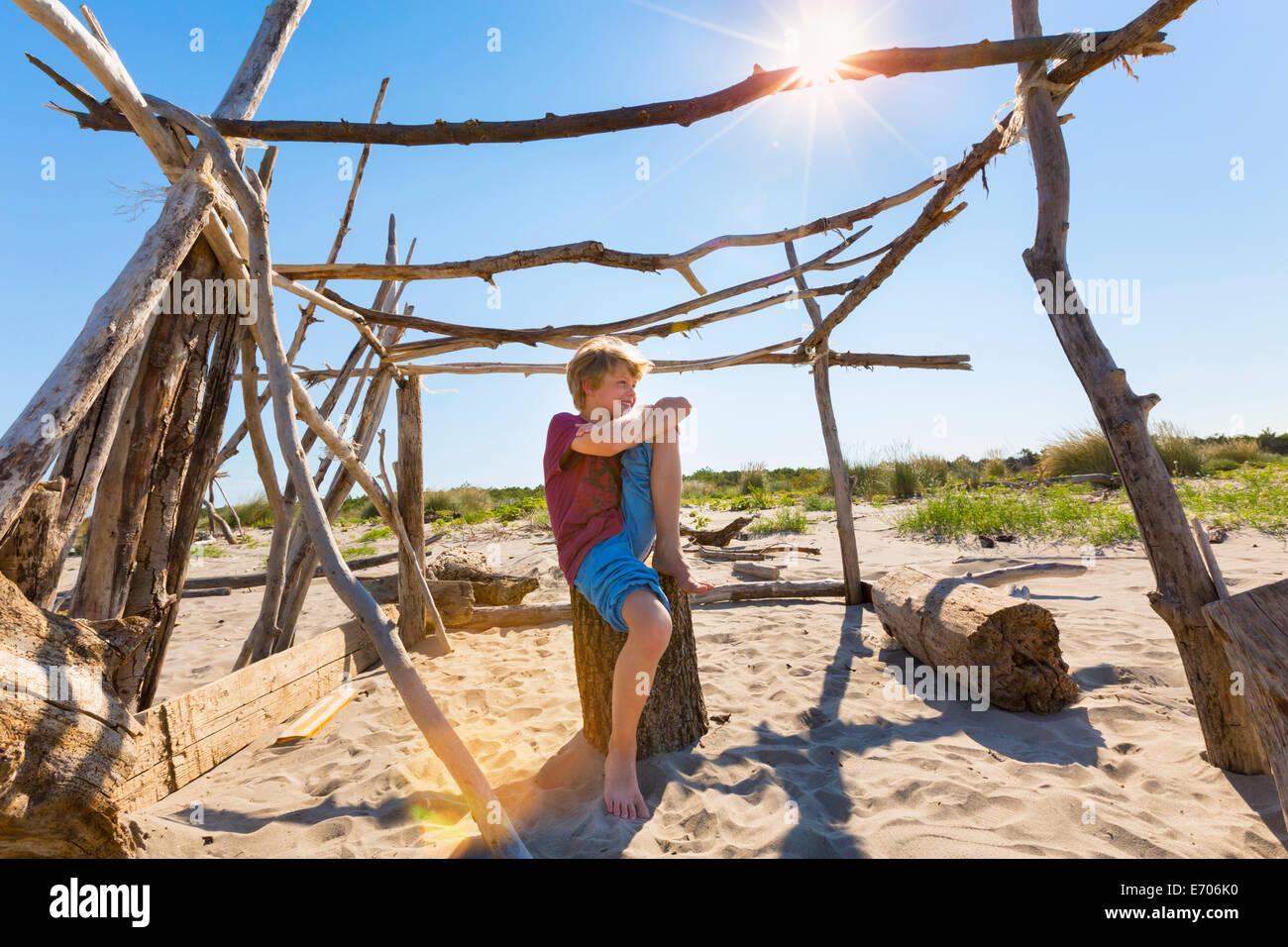 Boy making a break in driftwood shelter, Caleri Beach, Veneto, Italy - Stock Image