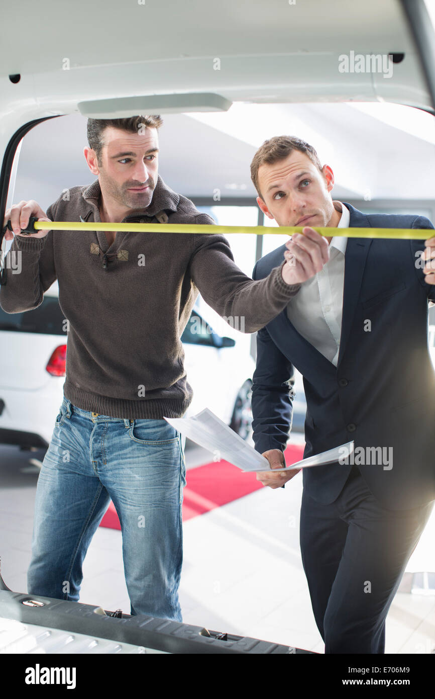 Customer and salesman measuring van interior in car dealership - Stock Image