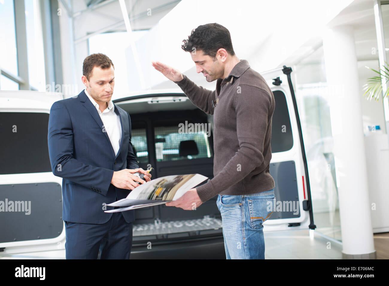 Customer questioning salesman in car dealership - Stock Image
