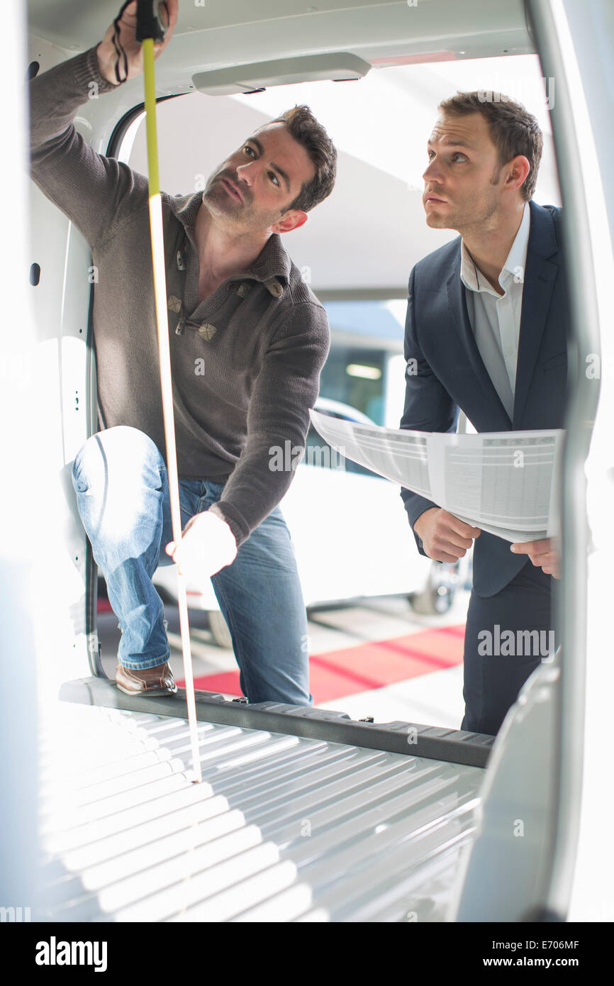 Customer and salesman checking vehicle interior height in car dealership - Stock Image