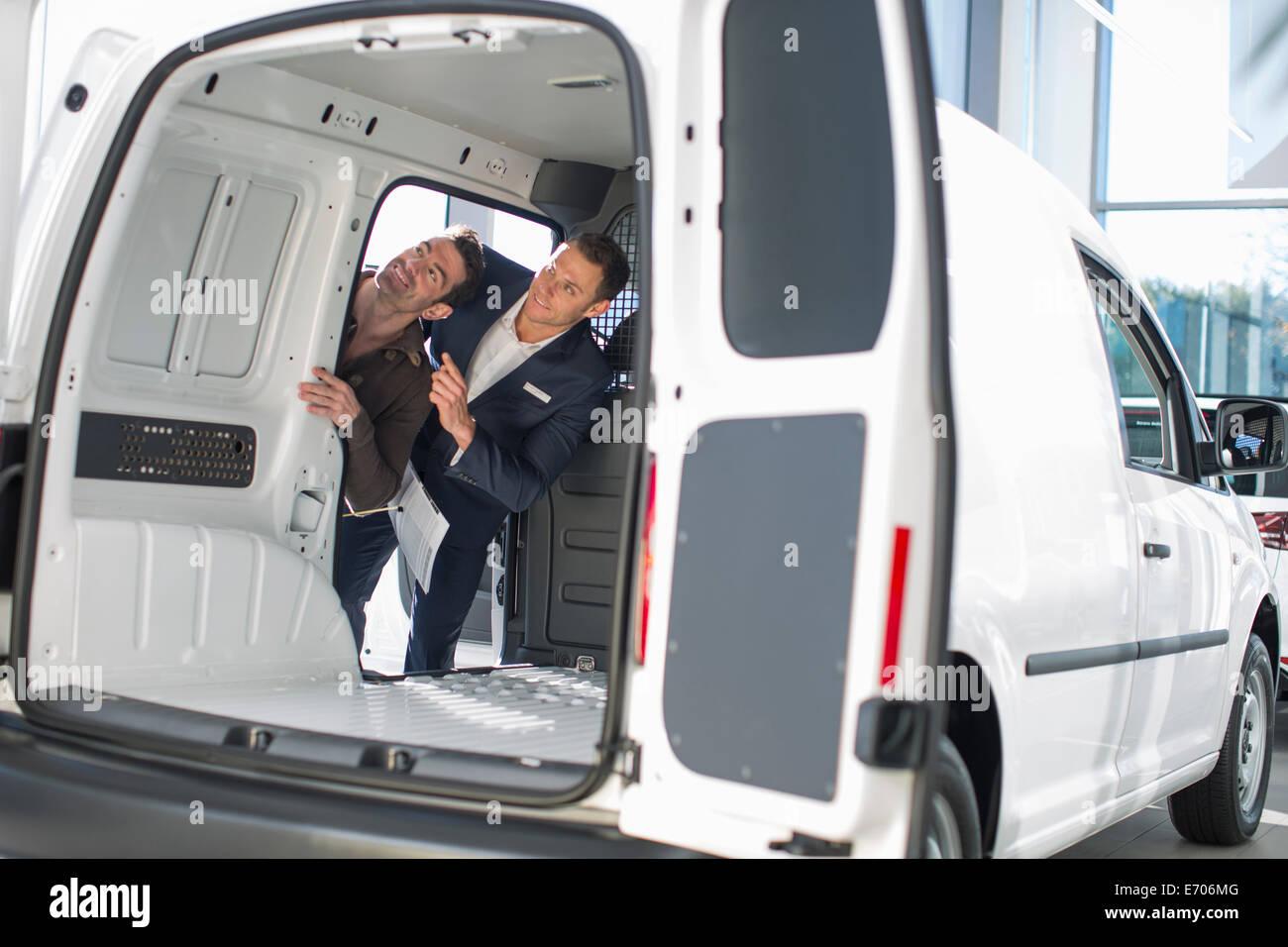 Customer and salesman checking vehicle interior in car dealership - Stock Image