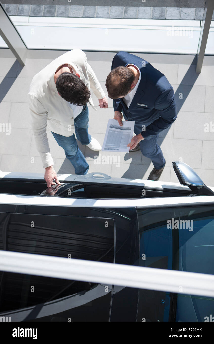 Overhead view of salesman and customer looking at new car in car dealership - Stock Image