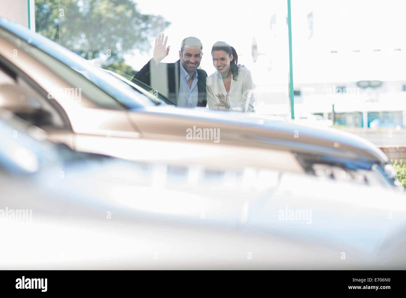 Mid adult couple looking through car dealership window - Stock Image