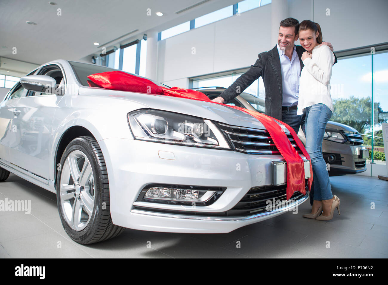 Man looking at new car with red bow with girlfriend in car dealership - Stock Image
