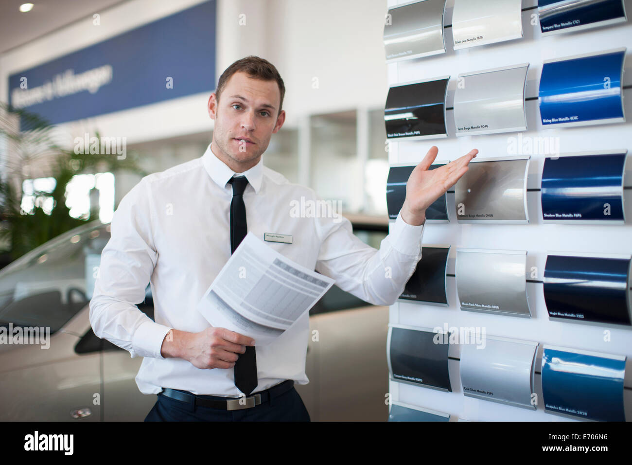 Portrait of salesman gesturing to color swatches in car dealership - Stock Image