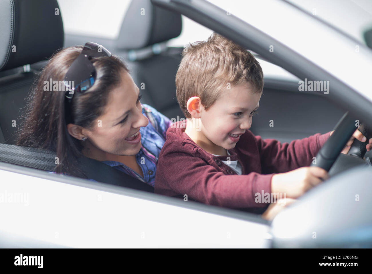 Mother and son trying out new car in car dealership - Stock Image