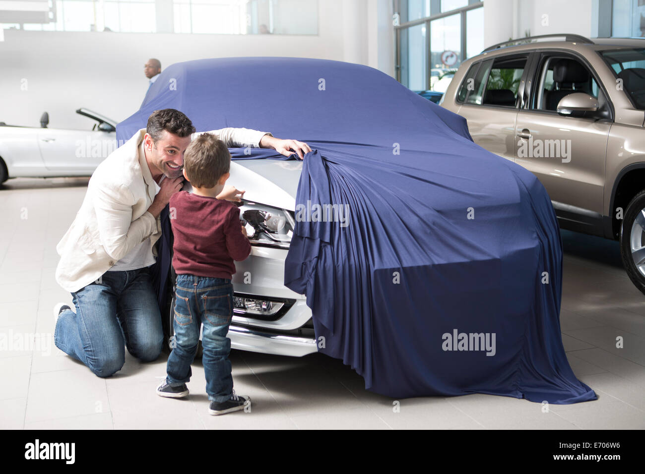 Mid adult man uncovering new car for son in car dealership - Stock Image