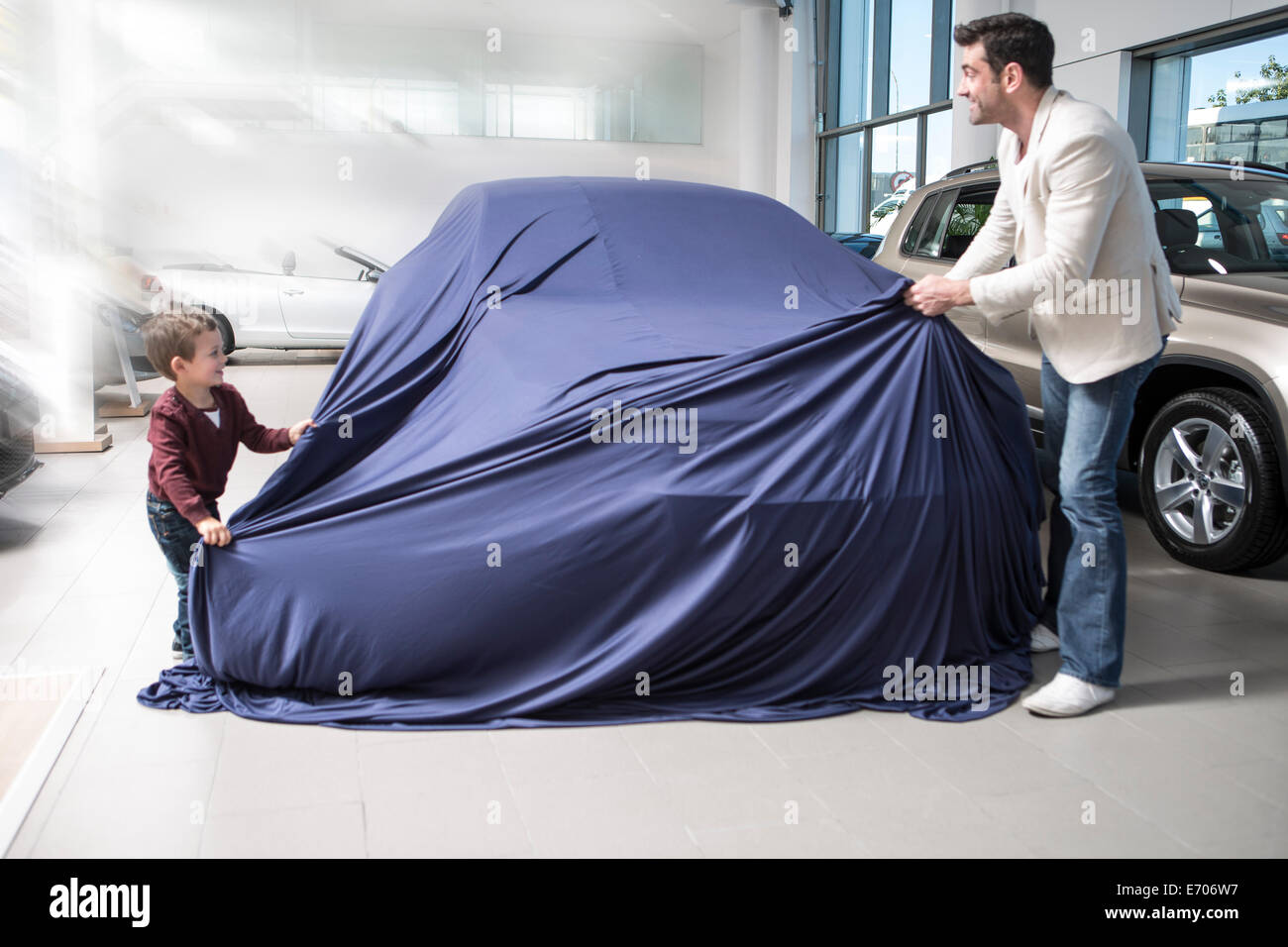 Mid adult man uncovering new car with son in car dealership - Stock Image