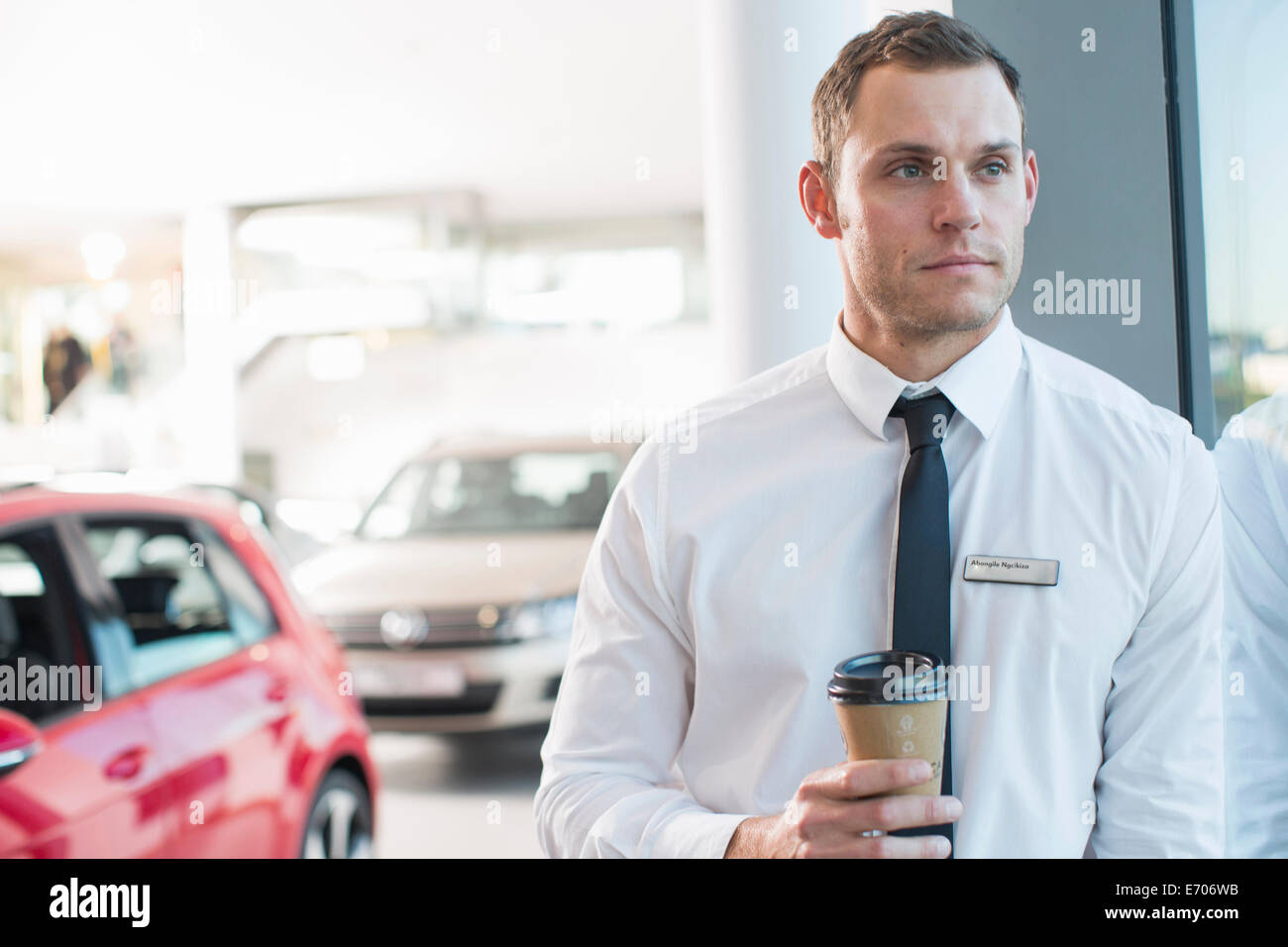 Portrait of worried salesman with takeaway coffee in car dealership - Stock Image