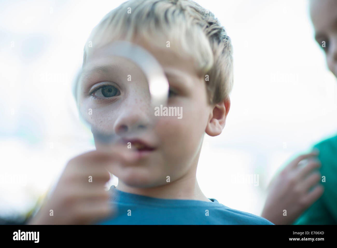 Portrait of boy holding magnifying glass in front of eye - Stock Image