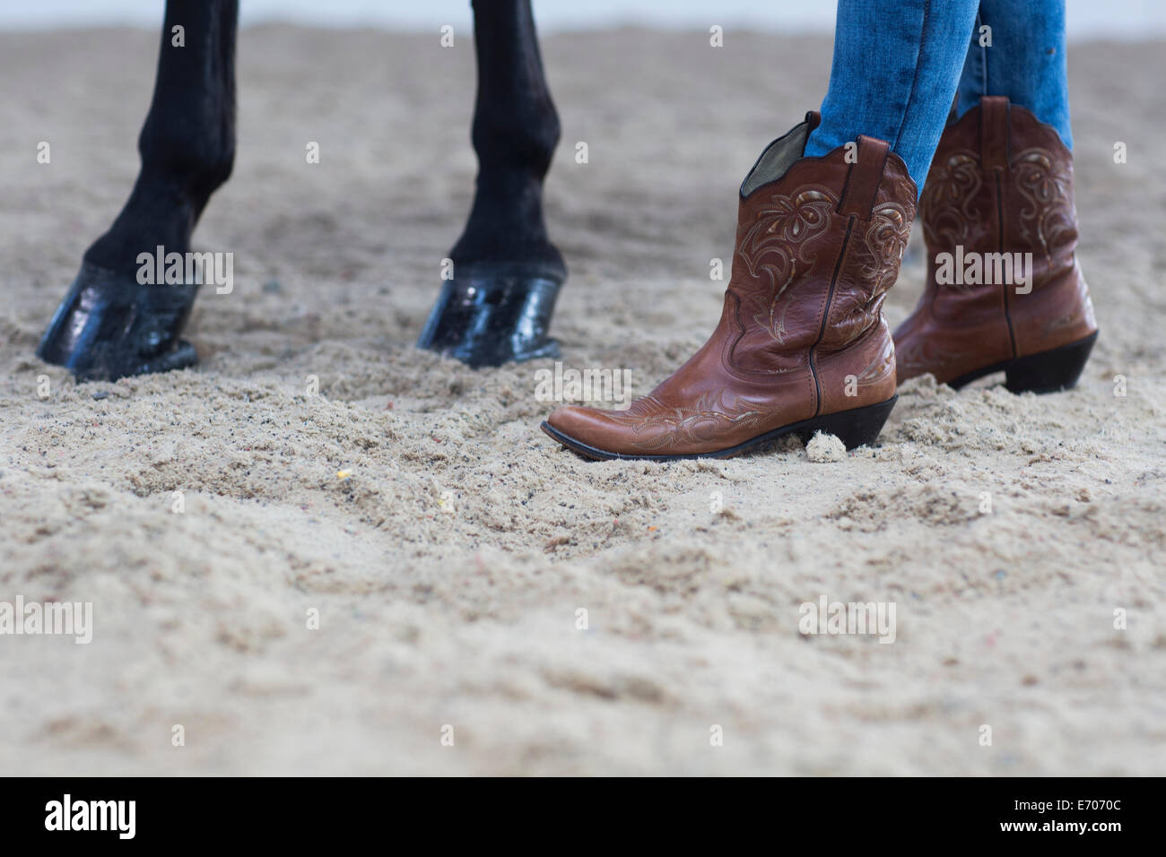 Cropped shot of horse hooves and young woman in cowboy boots - Stock Image