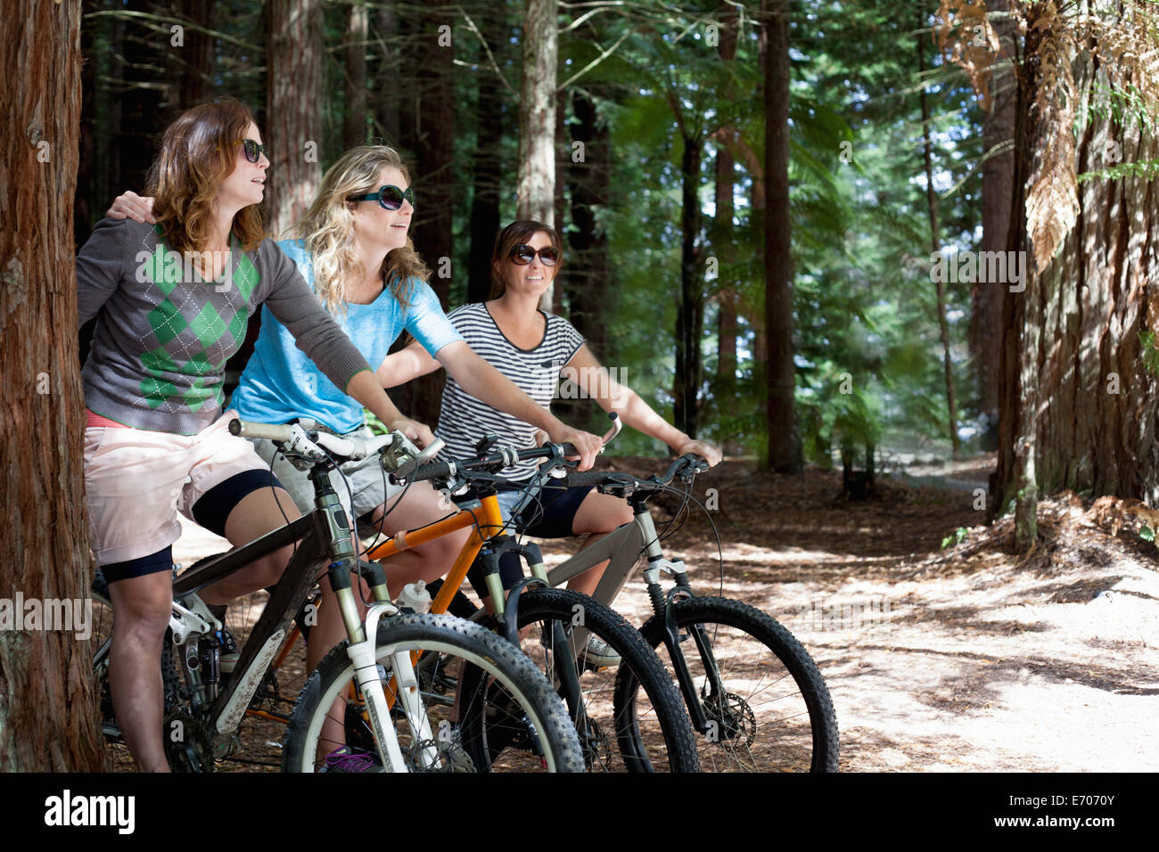 Portrait of three women mountain bikers in forest - Stock Image